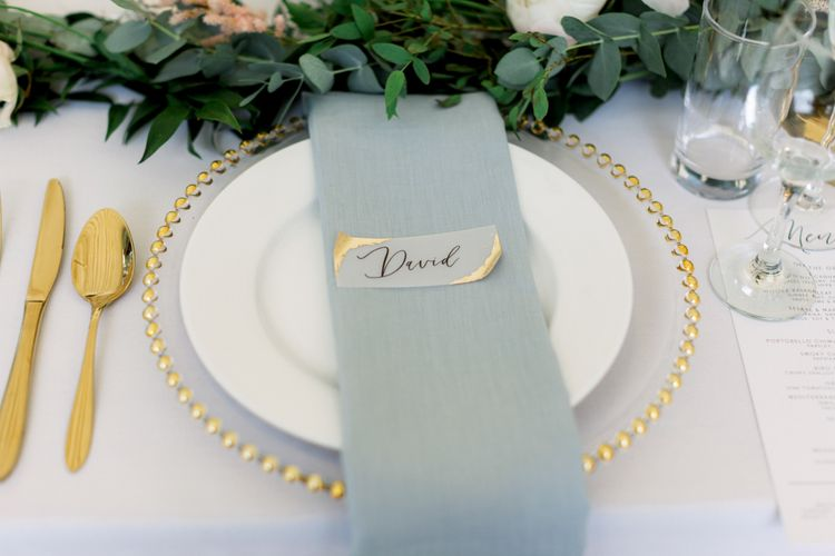 Place setting with blue napkin and gold cutlery