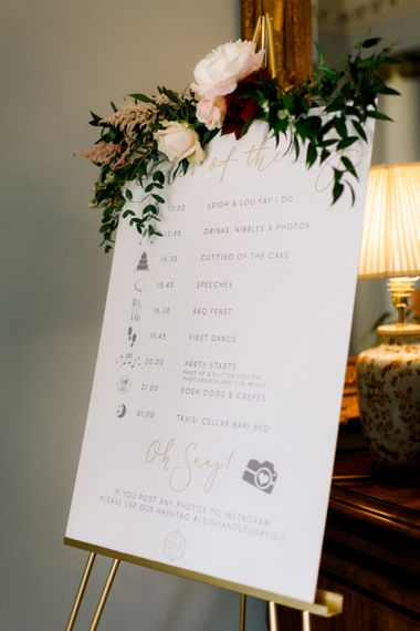 Order of the day wedding sign decorated in flowers