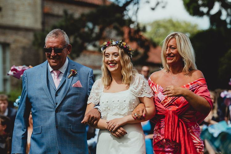 Bride walks down the aisle with parents wearing flower crown