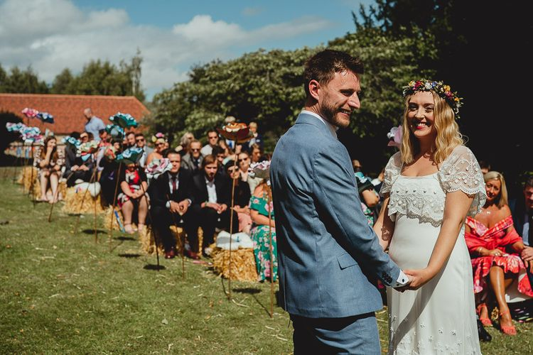 Bride and groom say I Do at outdoor ceremony with homemade flowers and bunting