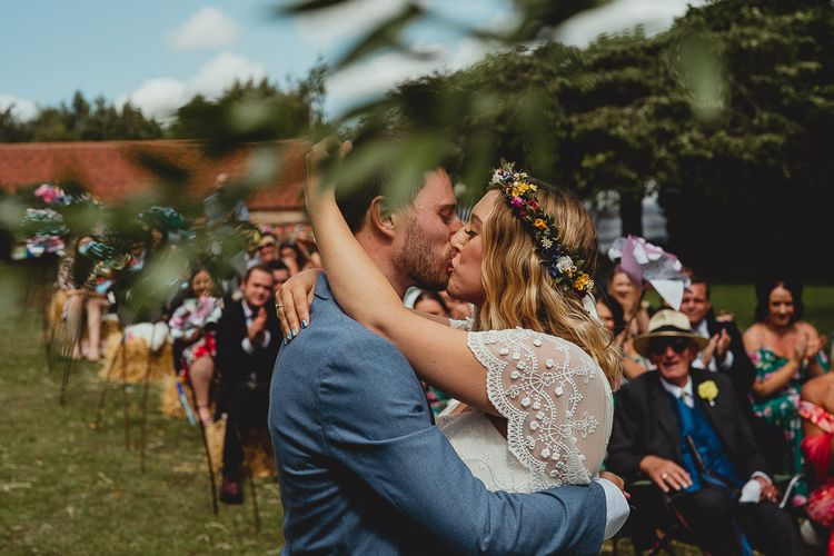Bride and groom kiss during outdoor ceremony at  Norfolk wedding venue