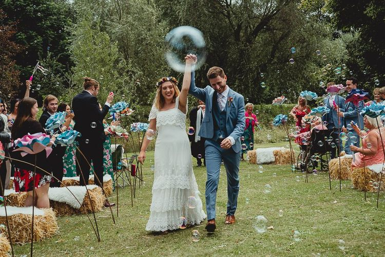 Bubble exit outdoor ceremony at  Norfolk wedding venue with wedding bunting and homemade flowers