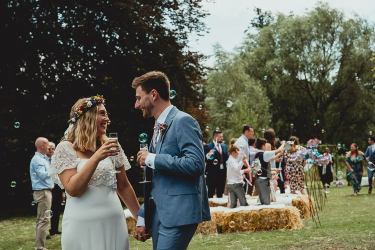 Bride and groom take a moment after ceremony with wedding bunting and homemade flowers