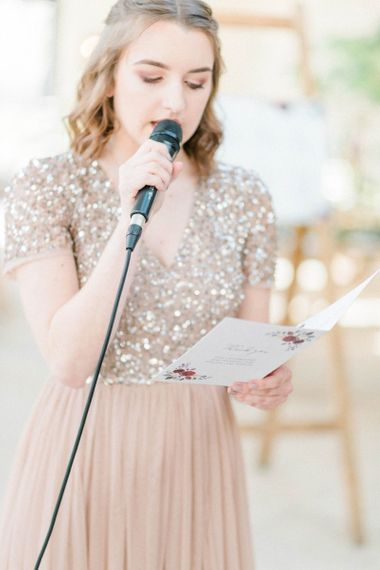 Bridesmaid in blush sequin dress giving a wedding reading