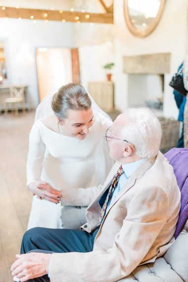 Bride greeting an older wedding guest at February wedding