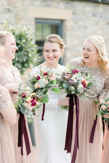 Bride and bridesmaids laughing together at February wedding