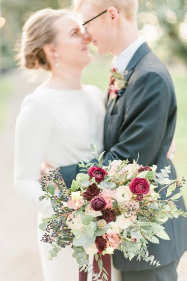 Winter wedding bouquet with deep red flowers and foliage