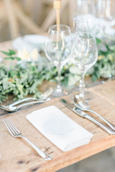 Minimalist place setting with greenery garland and silver cutlery