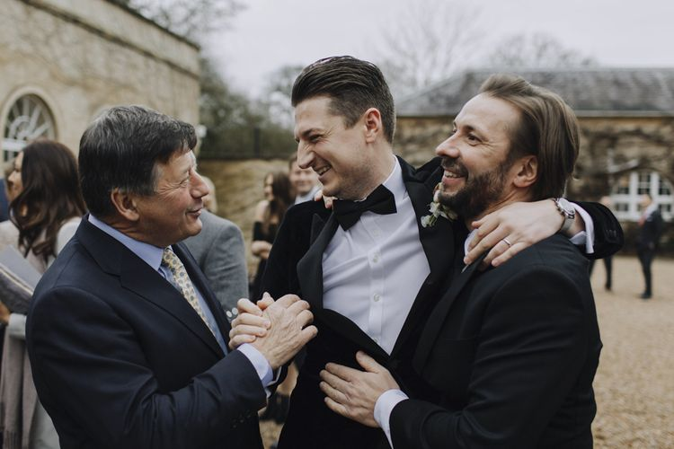 Groom in Black Tie Suit Being Congratulated by His Friends