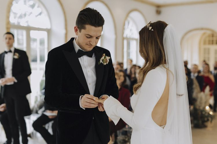 Bride in Emma Beaumont Wedding Dress and Groom in Tuxedo Exchanging Rings