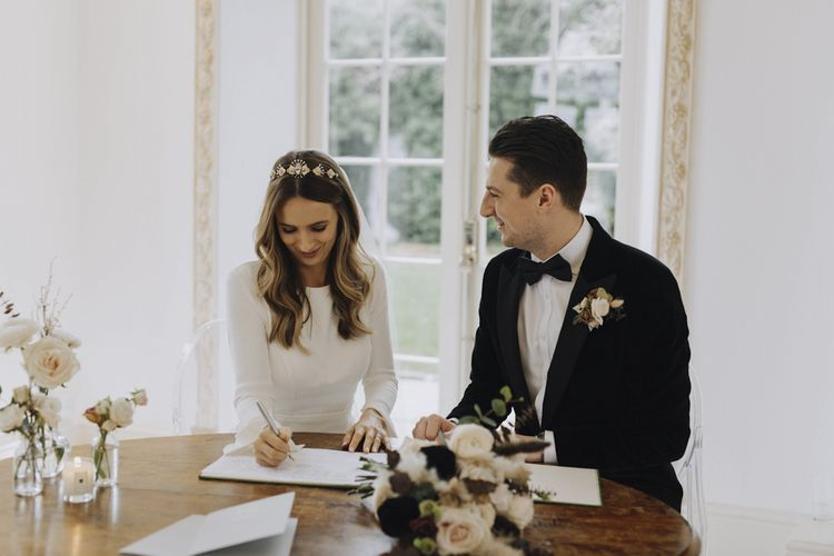 Bride in Emma Beaumont Wedding Dress and Tilly Thomas Lux Headdress and Groom in Black Tie Suit Signing the Register