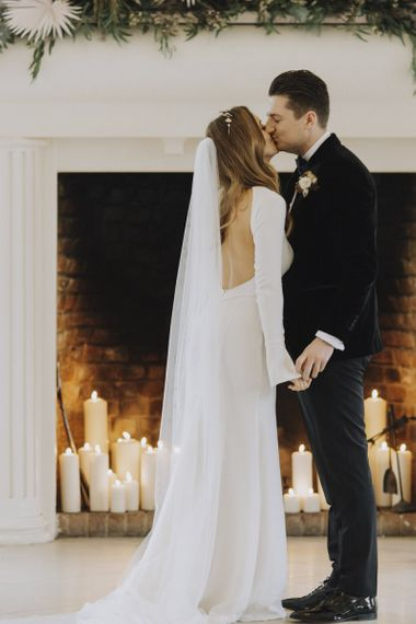 Bride in Backless Emma Beaumont Wedding Dress and Groom in Black Tie Suit Kissing at the Altar