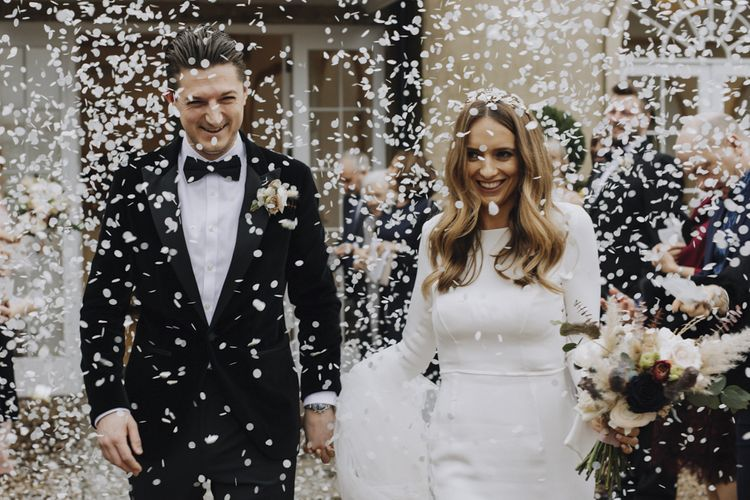 White Confetti Bomb Moment with Bride in Emma Beaumont Wedding Dress and Groom in Tuxedo