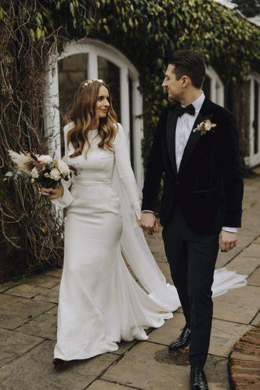 Bride in Emma Beaumont Wedding Dress and Groom in Tuxedo Walking Hand in Hand