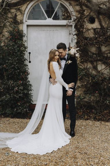 Bride in Backless Emma Beaumont Wedding Dress and Groom in Tuxedo Embracing