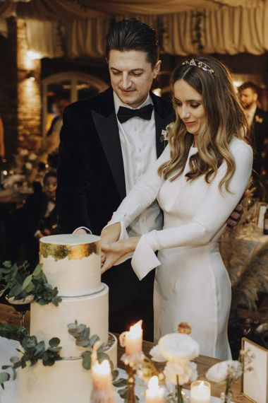 Bride in Emma Beaumont Wedding Dress and Groom in tuxedo Cutting The Wedding Cake