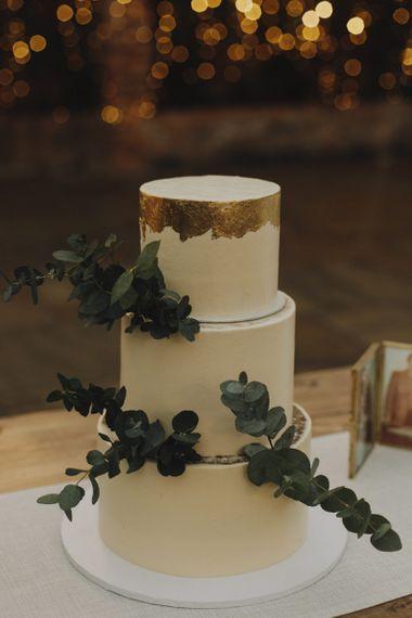 White Wedding Cake with Gold Leaf Detailing and Eucalyptus Decor