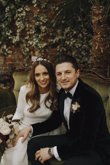 Bride in Emma Beaumont Wedding Dress and Groom in Tuxedo Sitting on an Ornate sofa