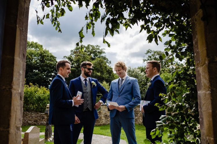 Groomsmen in Navy Blue Suits Standing Outside the Church