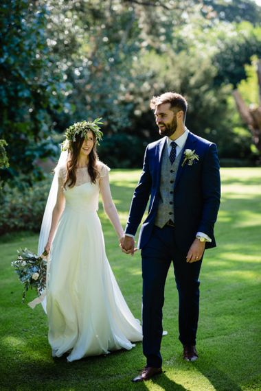 Bride in Charlie Brear Wedding Dress and Olive Flower Crown with Groom in Ted Baker Navy Suit Holding Hands