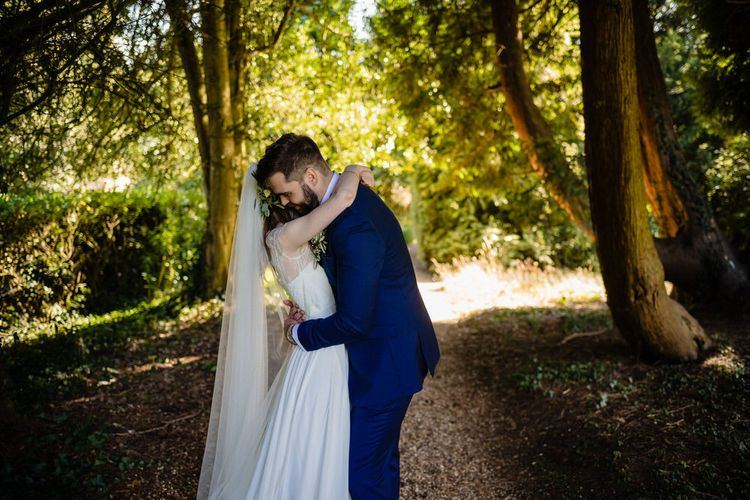 Bride in Charlie Brear Wedding Dress and Olive Flower Crown with Groom in Ted Baker Navy Suit Embracing