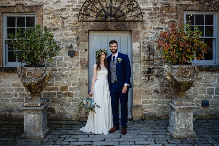 Bride in Charlie Brear Wedding Dress and Olive Flower Crown with Groom in Ted Baker Navy Suit Arm in Arm