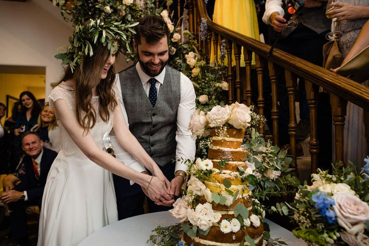 Bride in Charlie Brear Wedding Dress and Olive Flower Crown with Groom in Ted Baker Navy Suit Cutting the Naked Wedding Cake