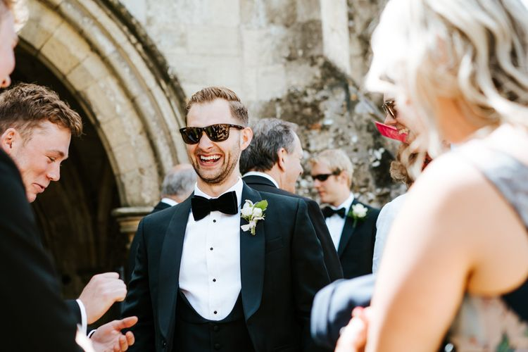 Groom in Black Tie Suit from Charles Tyrwhitt in the Church Courtyard