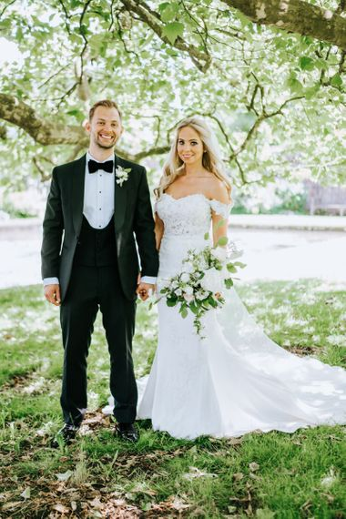 Bride in Lace St Partrick Wedding Dress with Groom in Black Tuxedo Suit