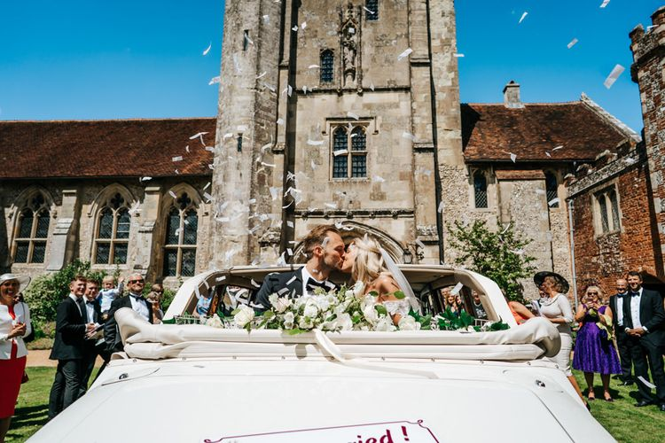 Bride and Groom on Convertible Wedding Car Covered in Confetti