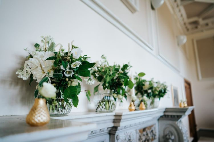 Fireplace Mantel Filled with Gold and Glass Vases filled with Green and White Flowers