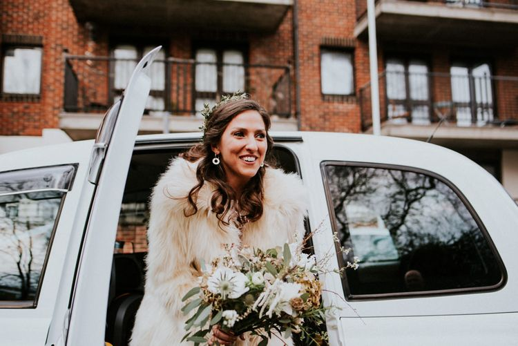 Bride Arriving in a White Cab in Grace Loves Lace Wedding Dress and Faux Fur Coat