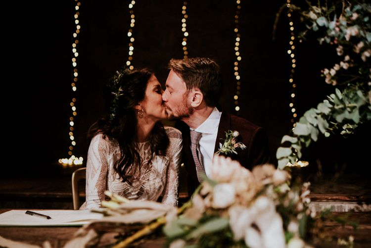 Bride in Grace Loves Lace Wedding Dress and Groom in  Brown Wedding Suit Kissing Whilst Signing The Register