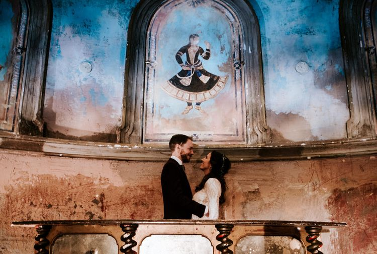 Bride in Grace Loves Lace Wedding Dress and Groom in Dark Suit Posing in Wilton's Music Hall