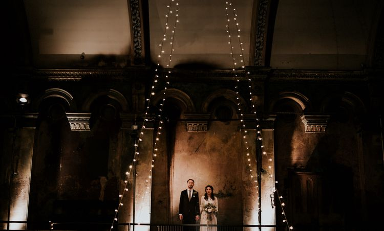 Bride in Grace Loves Lace Wedding Dress and Groom in Dark Suit Posing in Wilton's Music Hall with Fairy Lights
