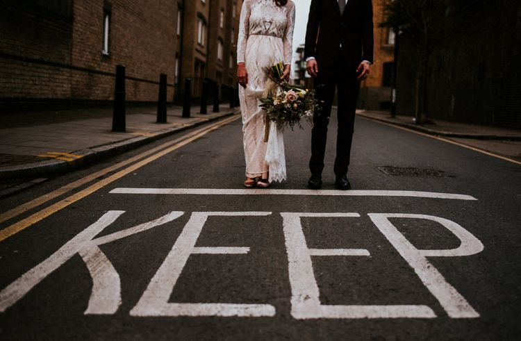 Urban Portrait of Bride in Grace Loves Lace Wedding Dress and Groom in Dark Suit Next to Keep Road Sign