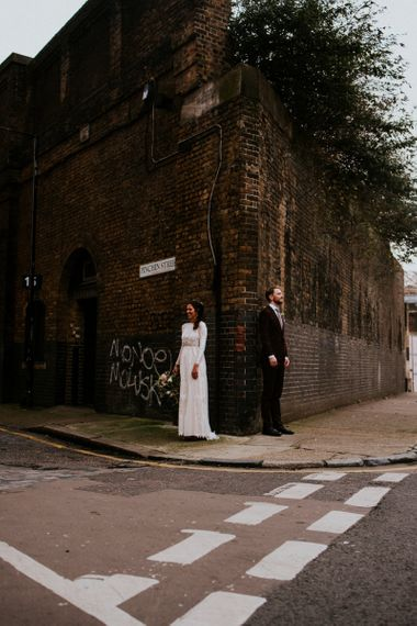 Urban Portrait of Bride in Grace Loves Lace Wedding Dress and Groom in Dark Suit on the Edge of a Corner