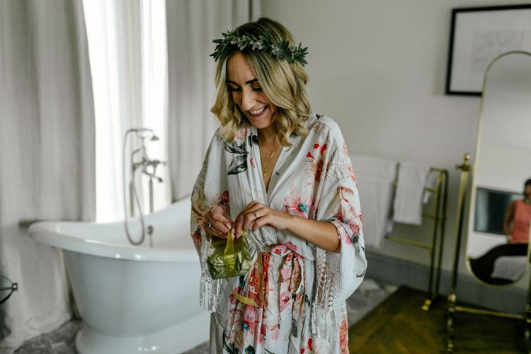 Bride on wedding morning in floral getting ready robe and flower crown