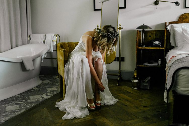 Bride putting on her gold platforms on wedding morning