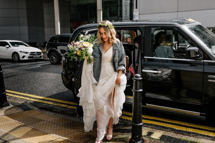 Bride arriving at Hackney Town Hall wedding in Catherine Deane wedding dress and denim jacket