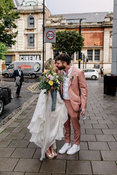 Bride and groom kissing outside Hackney Town Hall