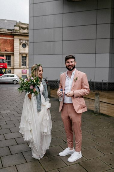 Stylish bride in wedding dress and denim jacket and groom in pink suit