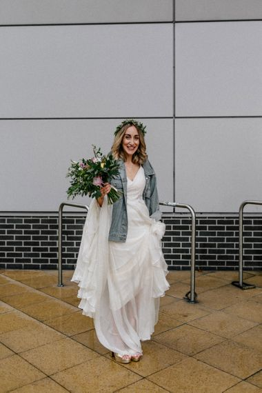 Stylish bride in Catherine Deane wedding dress and denim jacket