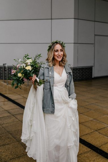 Bride in Catherine Deane wedding dress and denim jacket with flower crown and wedding bouquet
