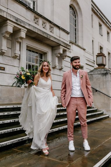Bride and groom on the steps at their Hackney Town Hall intimate wedding