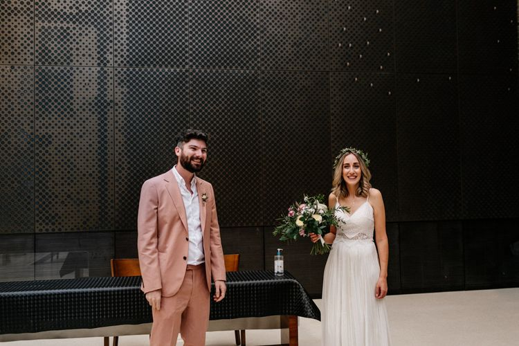 Stylish bride and groom at the altar of their Hackney Tow Hall wedding