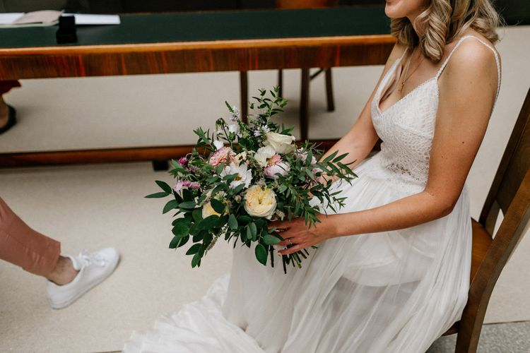 Bride in Catherine Deane wedding dress holding her bridal bouquet