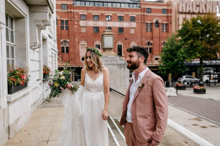 Stylish boho bride and groom in pink suit outside Hackney Town Hall