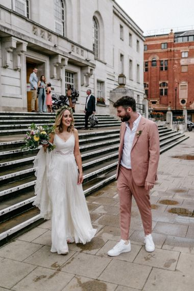 Boho bride in Catherine Deane wedding dress and groom in coloured suit at intimate city wedding