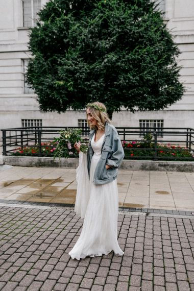 Stylish bride in Catherine Deane wedding dress, flower crown and denim jacket